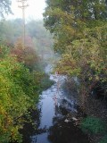 The creek running parallel to the railroad bed, on a foggy morning.