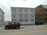 The Six West Apartments (#425), with the red vehicle in front of the mark.