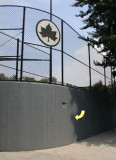 This high concrete wall surrounds the southeast corner of the ballfield.