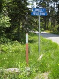 Monument, witness post and signs at the intersection of Arnold Road and Lighthouse Road, which leads down to Bass Harbor Head Lighthouse.