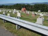 Looking W over cemetery, toward small chapel; West Mountain in background.