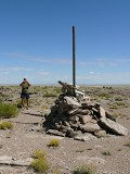 Station disk at base of cairn, and Rich taking a photo of the area.