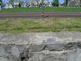 Eyelevel view of the reference mark disk set into the stone wall.