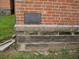 The mark is near a plaque designating the court house as an historic landmark.