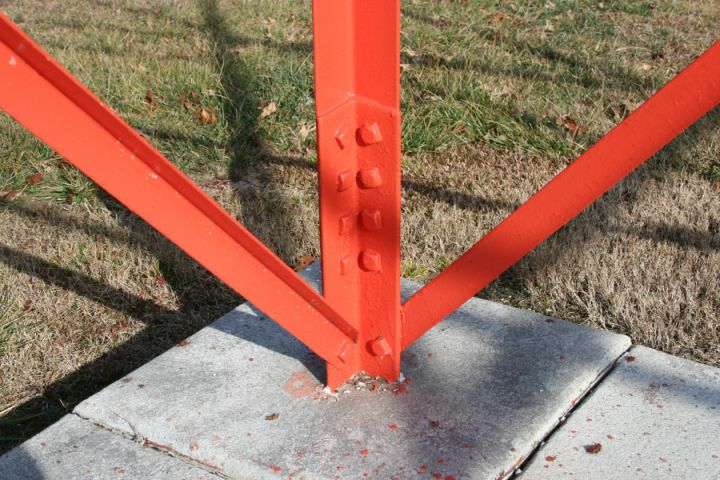 Close up of the base of the Crossville, TN airport beacon showing the stub set in concrete with the tower attached to by 4 bolts and a single bolt for brace attachment.