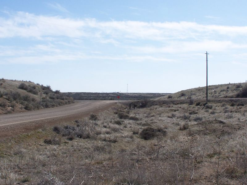 "Looking South to the intersection of Desert Wind Rd and Regina Rd. The name of the road is different from the name of the old town(?) shown on the topographic maps of the area, which call it out as Regena. Airway Map 135 also describes this as ""Regena""."